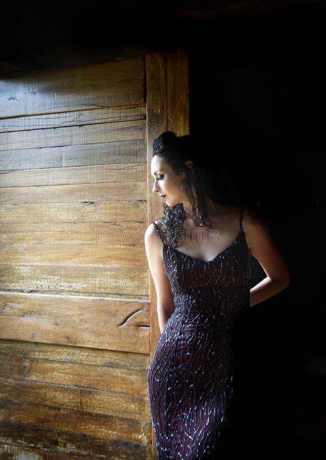Kvinna i rött anseende för aftonklänning i dörröppning fotografering för bildbyråer