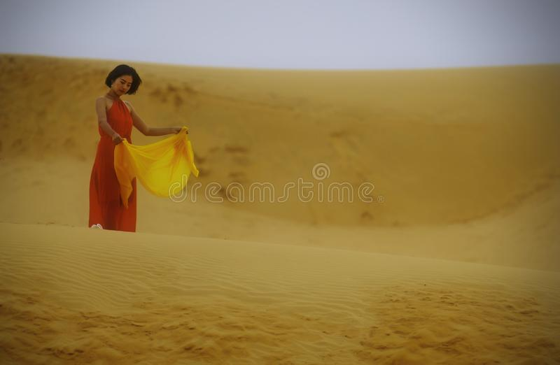 Kvinna i rött klänninganseende i öknen royaltyfria foton