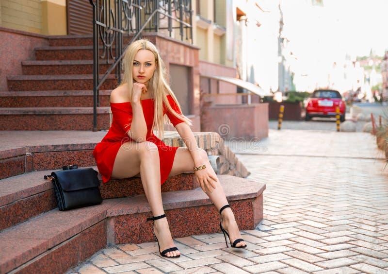 Kvinna i rött klänningsammanträde på trappan royaltyfri foto