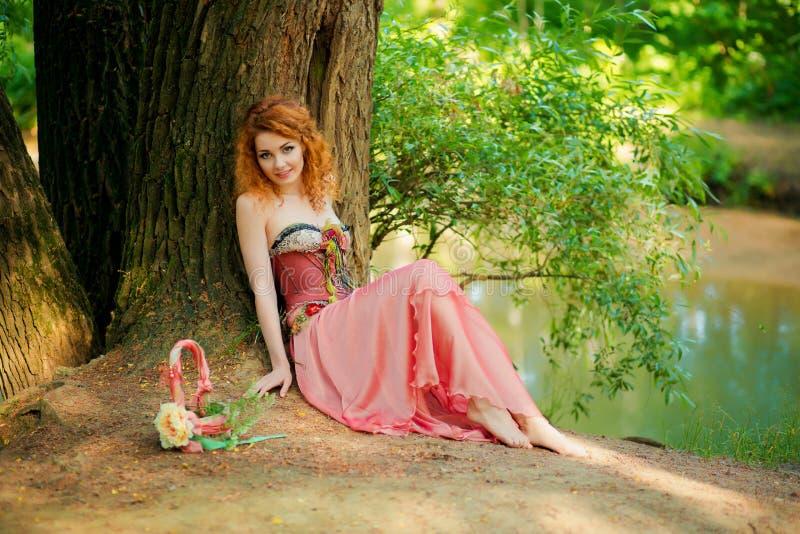 Kvinna i rött klänningsammanträde under ett träd på naturen arkivbild