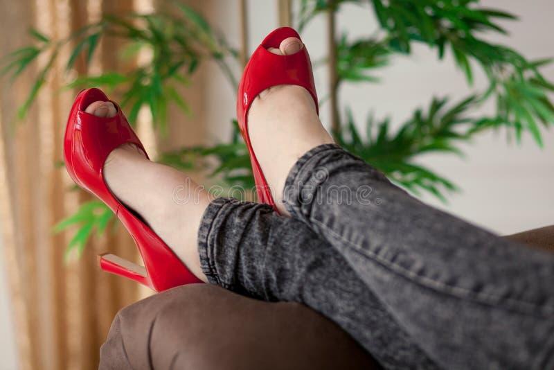 Kvinna i rött koppla av för sko arkivfoton