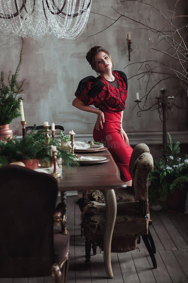 Kvinna i rött tappningklänninganseende vid beautifully uppsättningen som äter middag tabellen Vindinre med den klara betongväggen royaltyfria bilder