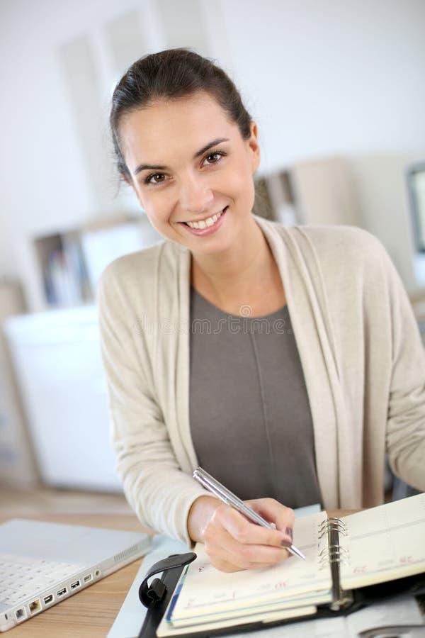 Kvinna i regeringsställning som skriver på dagordning arkivbild