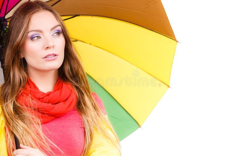 Kvinna i regntätt lag under paraplyet arkivbild