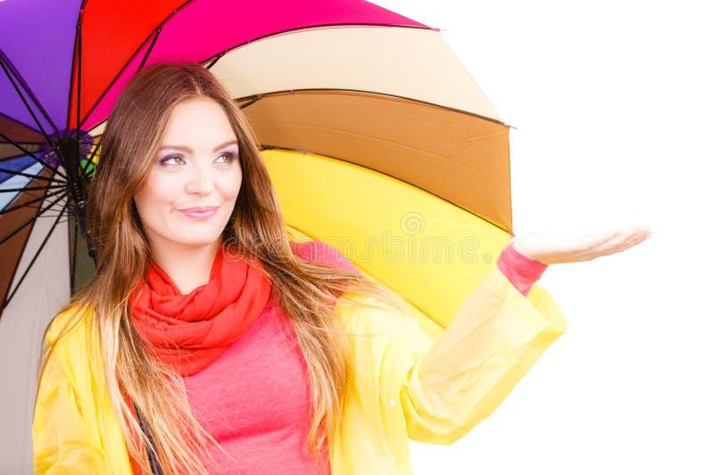 Kvinna i regntätt lag under paraplyet royaltyfri bild