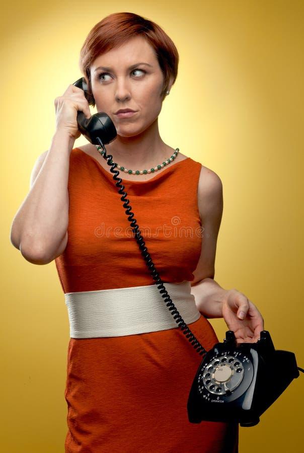 Kvinna i retro mode som svarar telefonen royaltyfria bilder