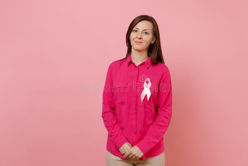 Kvinna i rosa kläder med rosa siden- bandsymbol på pastellfärgad väggbakgrund, studiostående läkarundersökning arkivfoton