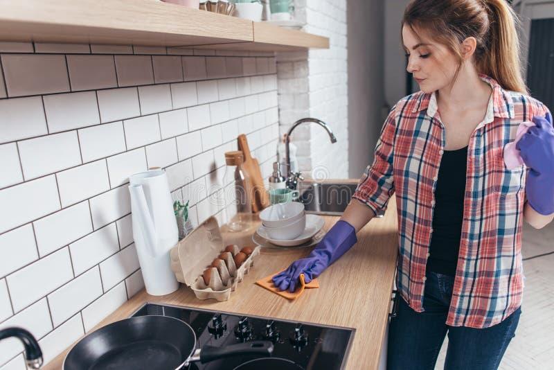 Kvinna i rubber handskar som gör ren köksbordet arkivbild