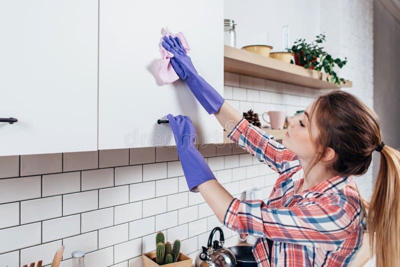 Kvinna i rubber handskar som gör ren köksskåpet royaltyfri fotografi