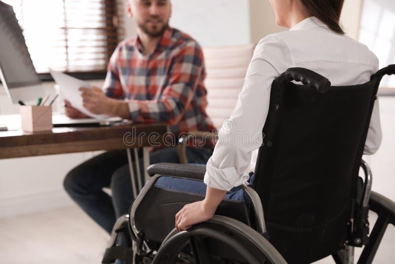 Kvinna i rullstol med hennes kollega på arbetsplatsen fotografering för bildbyråer