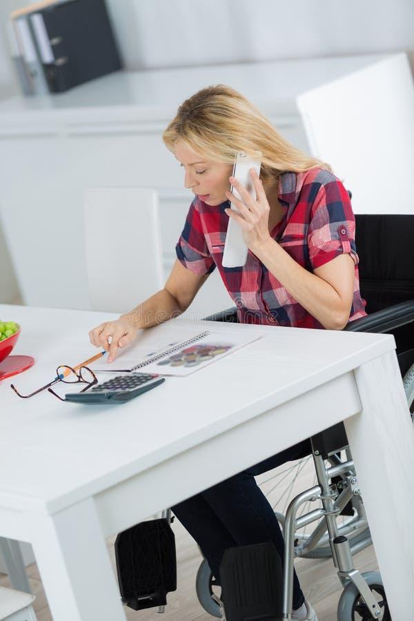 Kvinna i rullstoldanandeappell p? mobiltelefonen hemma fotografering för bildbyråer