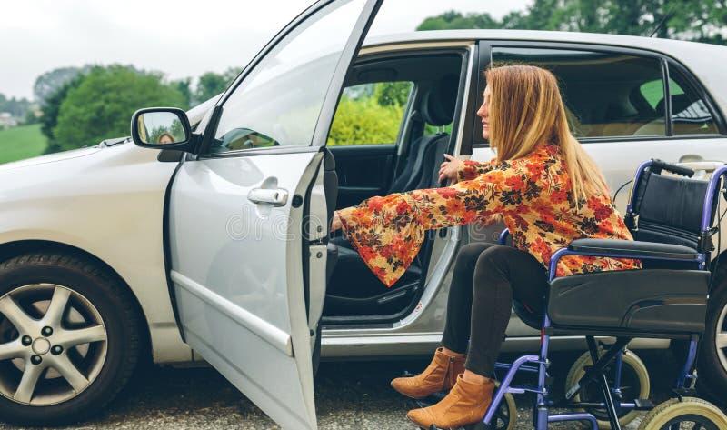 Kvinna i rullstolen som får på bilen arkivbild