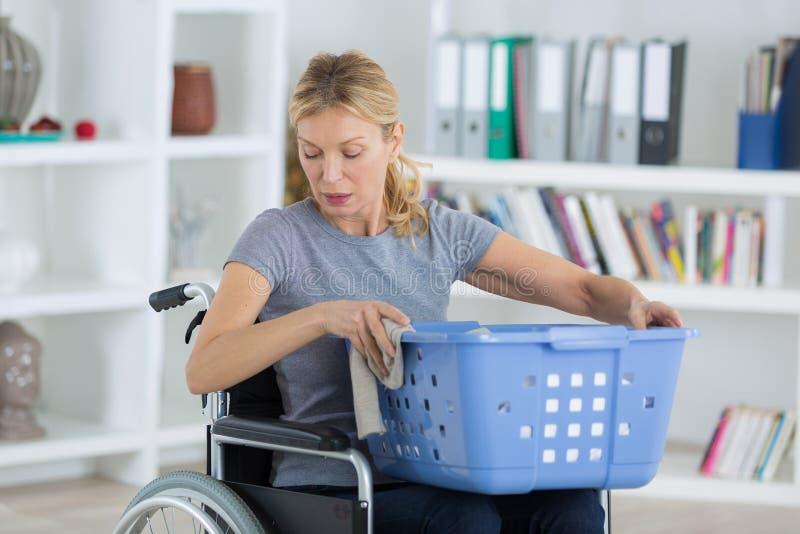 Kvinna i rullstolen som gör tvätterit royaltyfri foto