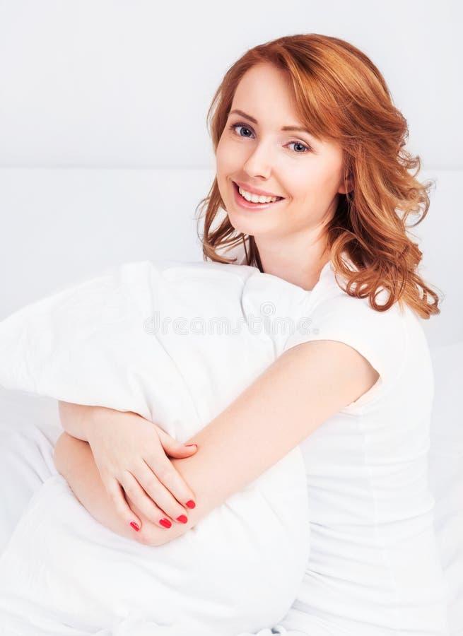 Kvinna i säng arkivfoto