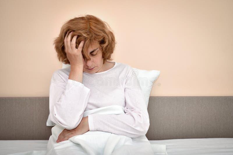 Kvinna i säng med huvudvärken som rymmer hennes huvud arkivfoton