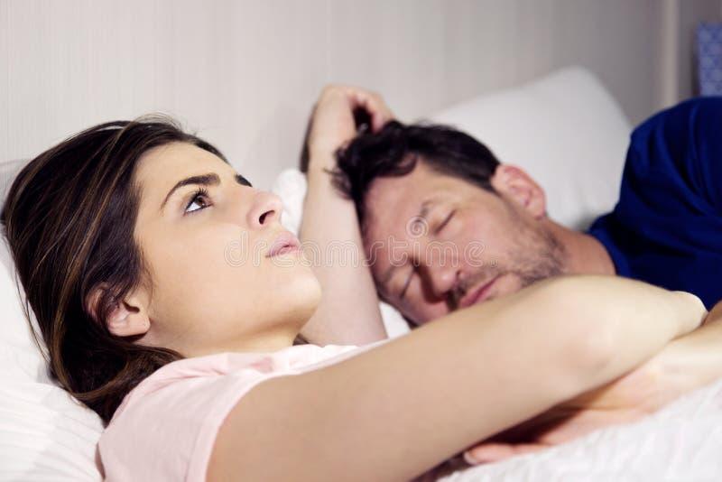 Kvinna i säng med pojkvännen som tänker om förhållande, medan mannen sover royaltyfria foton
