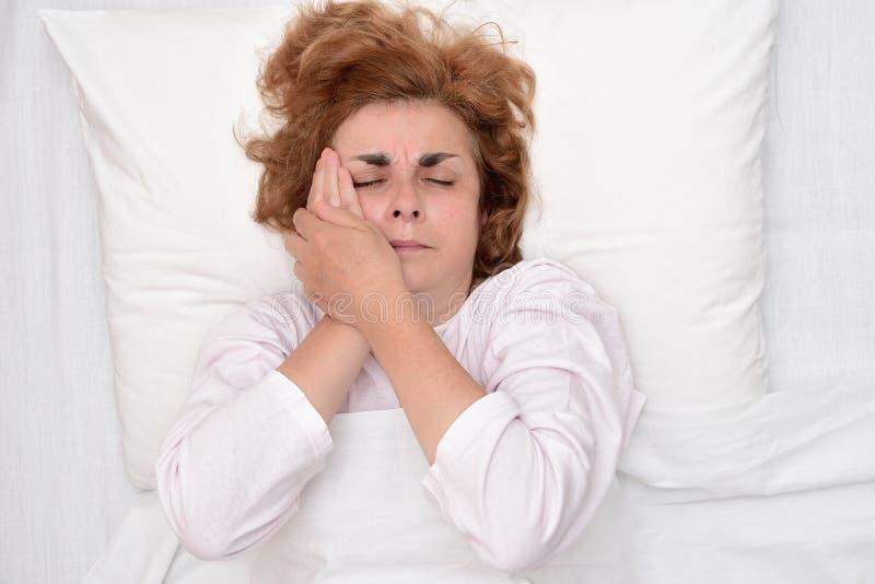 Kvinna i säng med tandvärk som rymmer hennes kind arkivbild