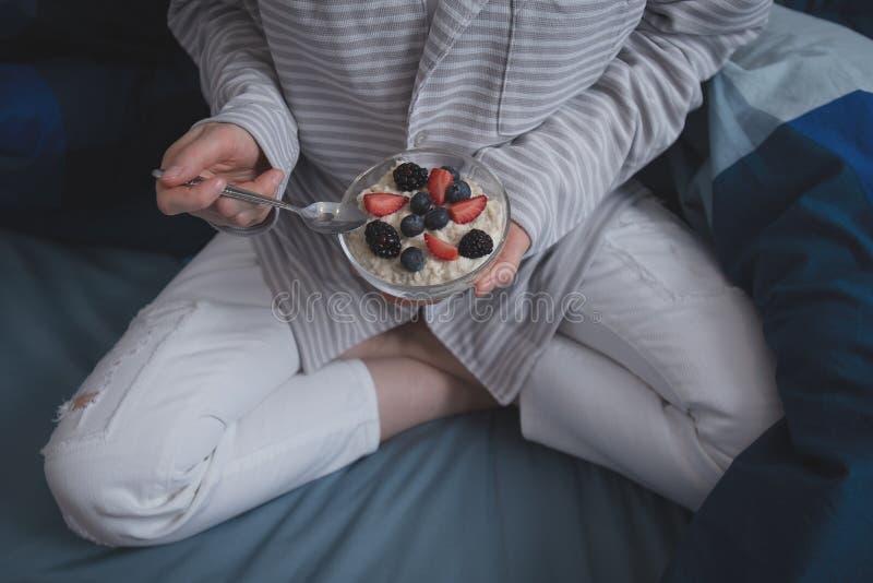 Kvinna i säng som äter havremjölhavregröt med lösa bär royaltyfria bilder