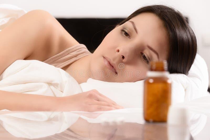 Kvinna i säng som synar en flaska av läkarbehandlingen royaltyfri fotografi