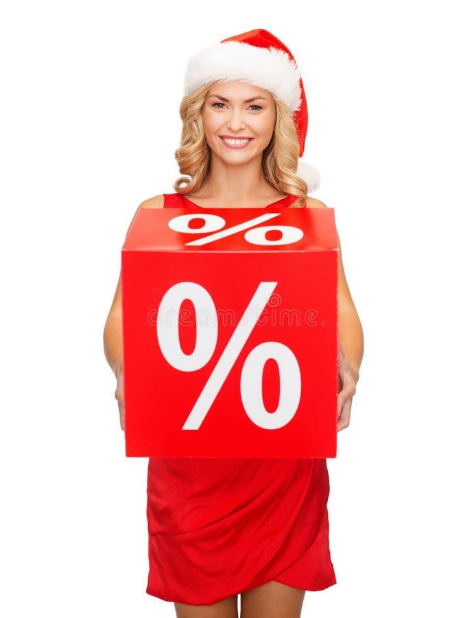 Kvinna i santa hjälpredahatt med det röda försäljningstecknet royaltyfria foton