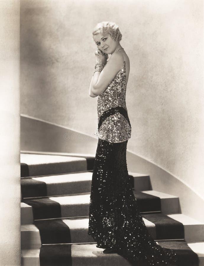 Kvinna i sequined kappaanseende på trappuppgång royaltyfri foto