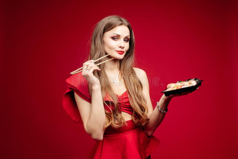 Kvinna i sexig röd klänning som äter den smakliga sushi i studio arkivfoto