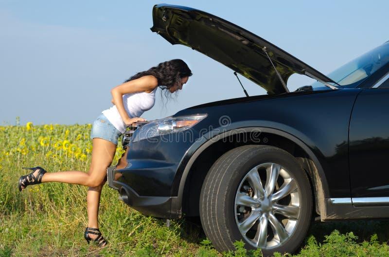 Kvinna i sexiga kortslutningar som kontrollerar motorn arkivbild