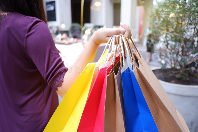 Kvinna i shopping Lycklig kvinna med färgrika shoppa påsar som tycker om att shoppa royaltyfri foto