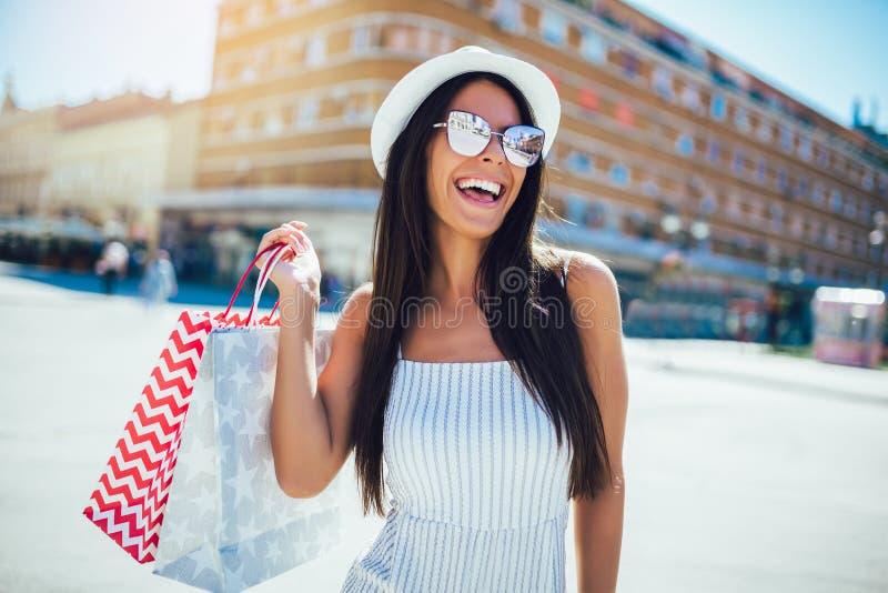 Kvinna i shopping Lycklig kvinna med shoppingp?sar som tycker om i shopping arkivfoto