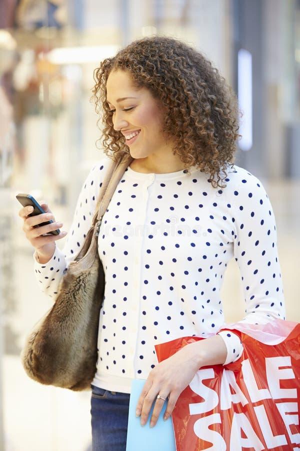Kvinna i shoppinggalleria genom att använda mobiltelefonen royaltyfria bilder