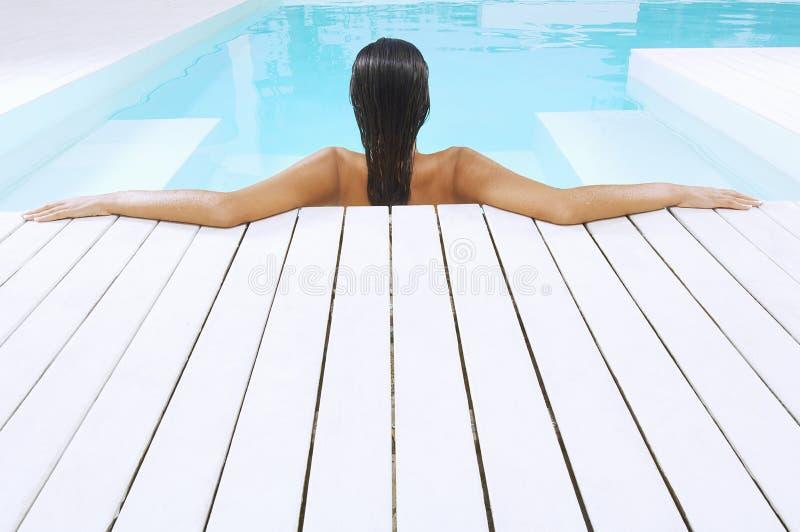 Kvinna i simbassängen som vilar på Poolside arkivbild