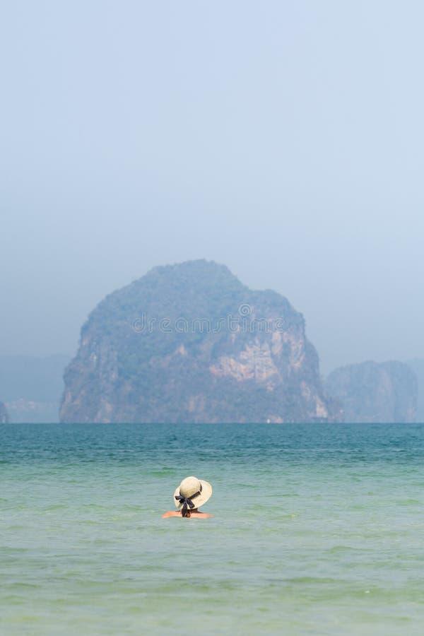 Kvinna i simning för sugrörhatt i havet i den Krabi Railey stranden som förbiser hamnen och bergen, Thailand royaltyfri fotografi