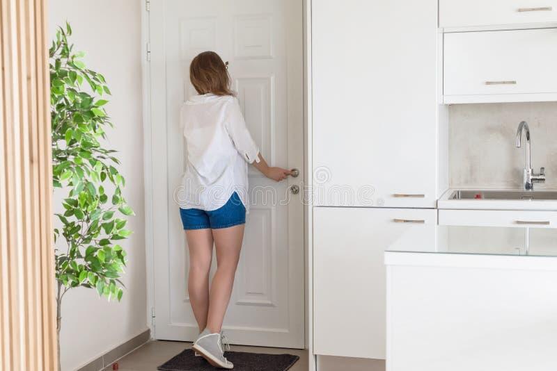 Kvinna i skjorta och kortslutningar som ser i kikhåldörr, när något ringer ringklockan royaltyfri fotografi