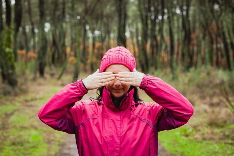 Kvinna i skogen som täcker henne ögon arkivbild
