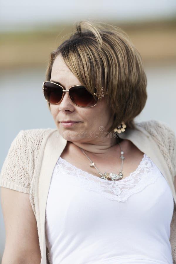 Kvinna i solglasögon bredvid sjön royaltyfria bilder