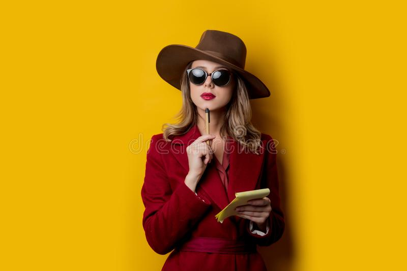 Kvinna i solglasögon med anteckningsboken och pennan royaltyfri foto
