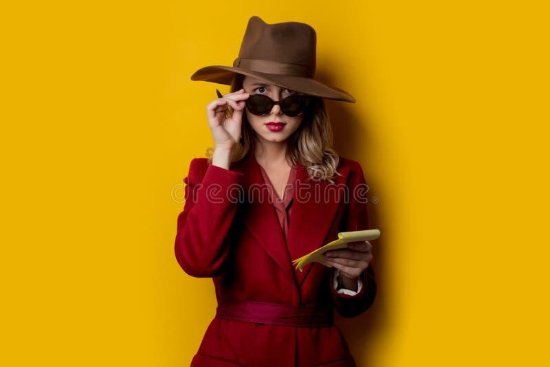 Kvinna i solglasögon med anteckningsboken och pennan arkivfoton