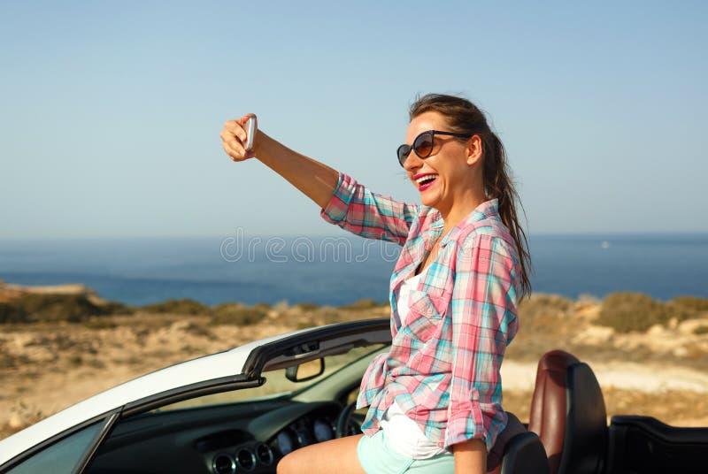 Kvinna i solglasögon som gör självståendesammanträde i cabriolen arkivbild