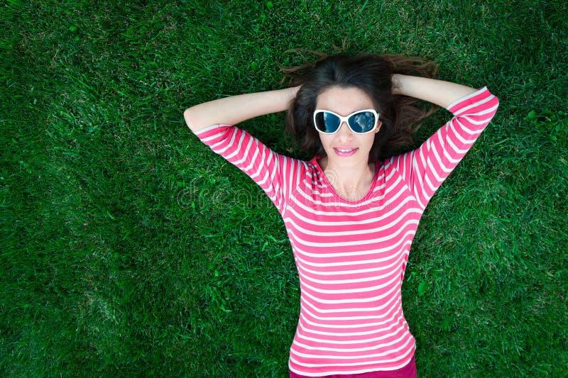 Kvinna i solglasögon som ligger på gräset arkivbild