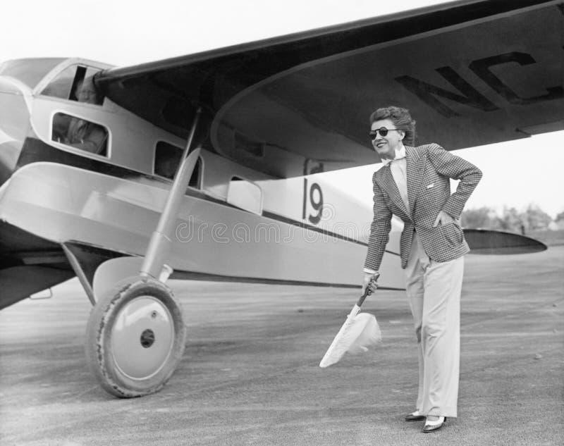 Kvinna i solglasögon som vinkar en flagga på grova asfaltbeläggningen bredvid ett flygplan (alla visade personer inte är längre u royaltyfri bild