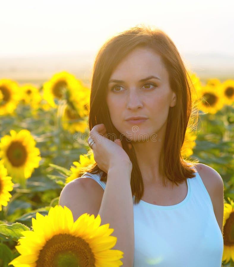 Kvinna i solrosfält på solnedgångtid royaltyfri bild