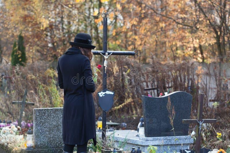 Kvinna i sorg på kyrkogården royaltyfria bilder