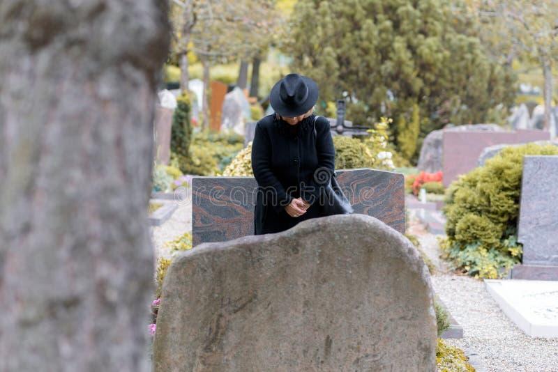 Kvinna i sorg som ber på en graveside arkivbilder