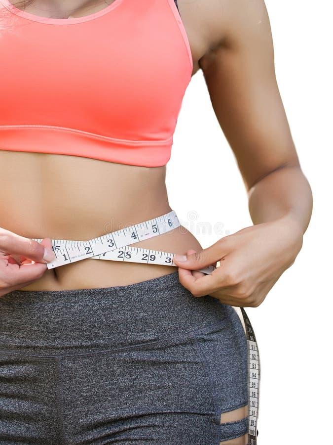Kvinna i sportbehå som mäter hennes kropp med bandet som isoleras på vit arkivfoto
