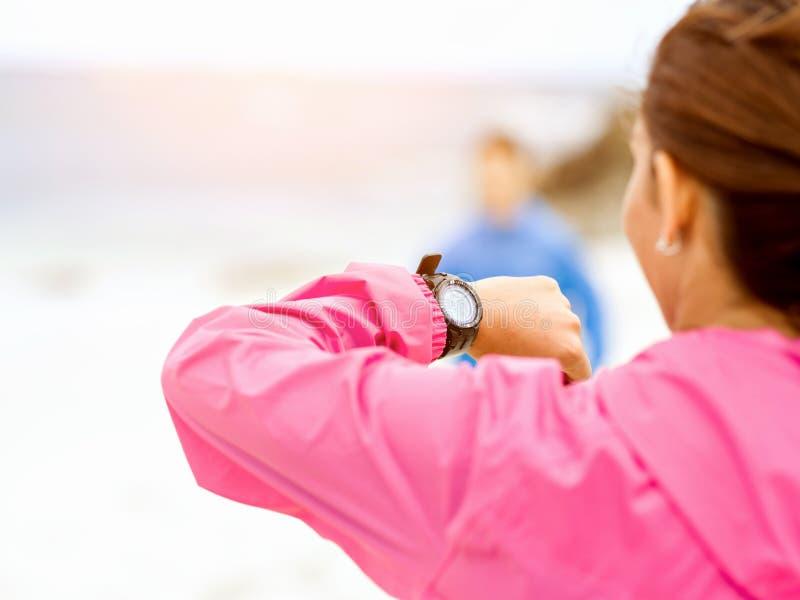 Kvinna i sportswear genom att använda smartwatch arkivfoton
