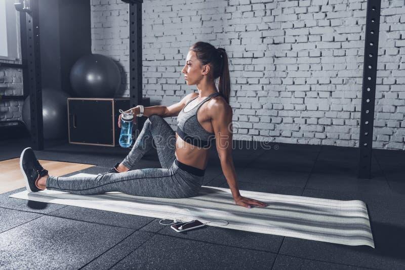 kvinna i sportswear med den sportive vattenflaskan i hand som vilar på mattt, når utbildning royaltyfria foton