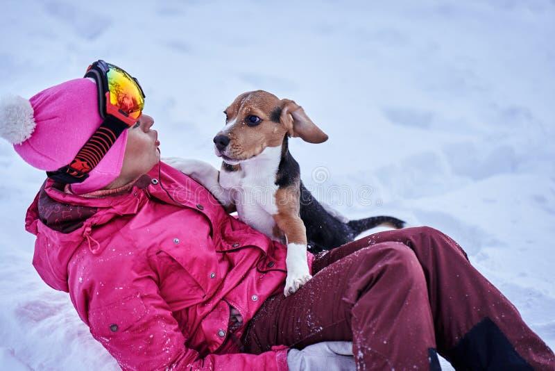 Kvinna i sportswearen som spelar med en valphund på snön royaltyfri fotografi