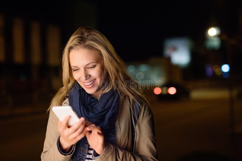 Kvinna i staden på den hållande smartphonen för natt som smsar arkivbild