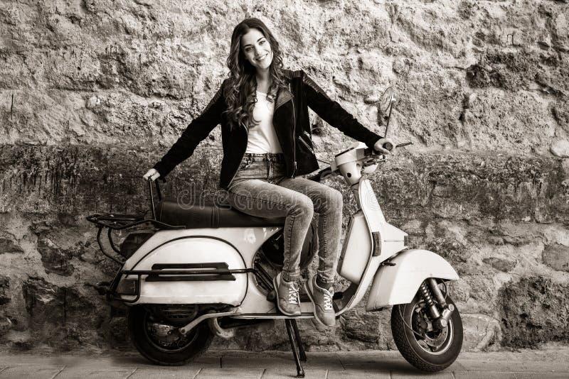 Kvinna i stads- bakgrundskvinnaklättring på en sparkcykel fotografering för bildbyråer