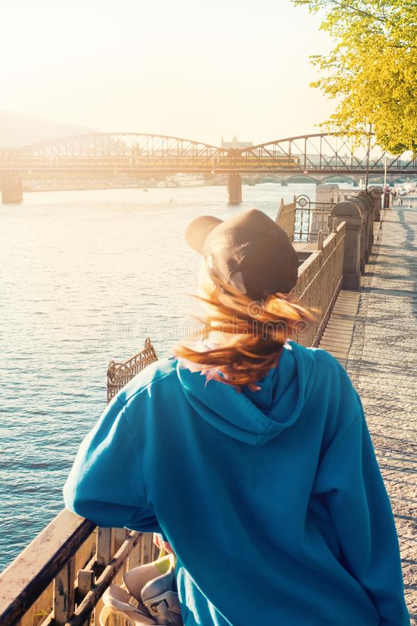 Kvinna i stadsanseendet bredvid floden Hon ser till floden Färgrikt foto av staden Solnedgång i landet royaltyfria foton
